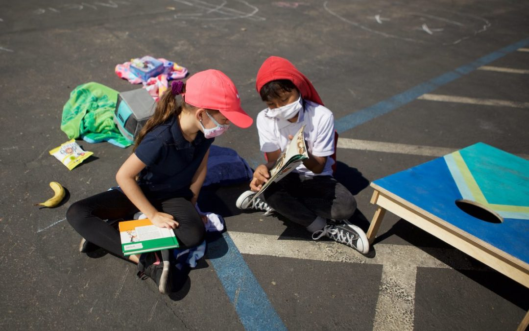 Two students at Empower Language Academy share a story outside