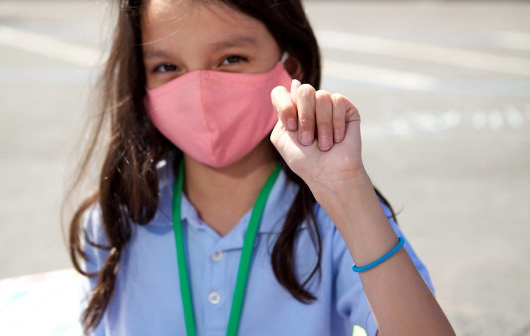 Empower Language Academy student wearing a face mask gives the sign to remind students to cover their noses with their masks.