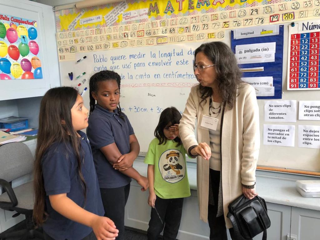 Three Empower Language Academy students lead a tour of a classroom for an adult community member