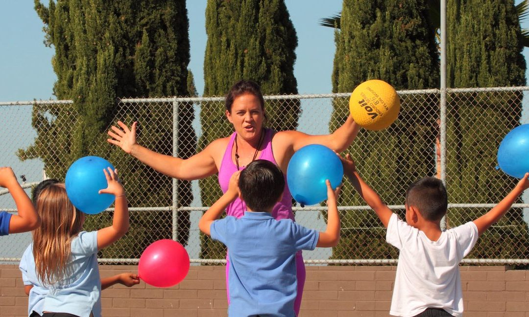 Feature Photo: Empower2.jpg Alt Text: Empower Language Academy CrossFit Kids teacher and 4 students participate in an activity using large colorful balls