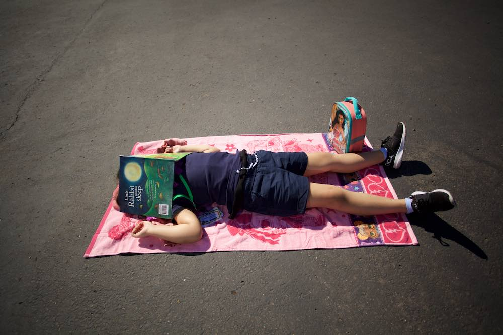 An Empower Language Academy student rests outside on a towel with a book over her face.