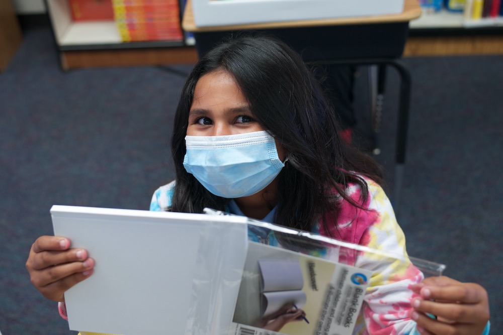 An Empower Language Academy student wearing a mask smiles at the camera