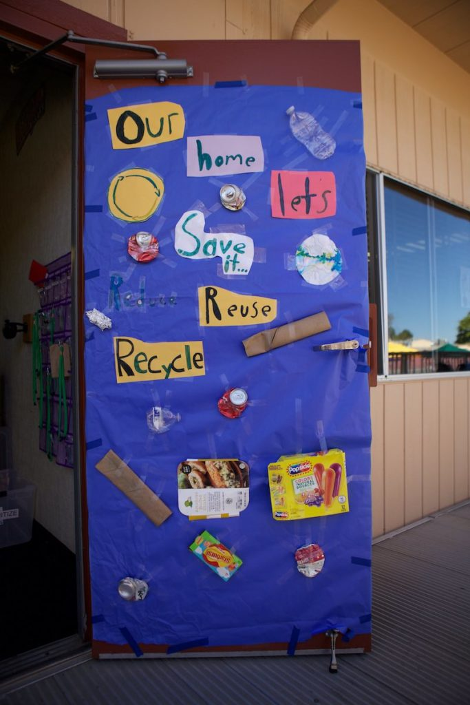 A classroom door Empower Language Academy decorated with a sign that says Our Home Lets Save It Reuse Recyle and child created art