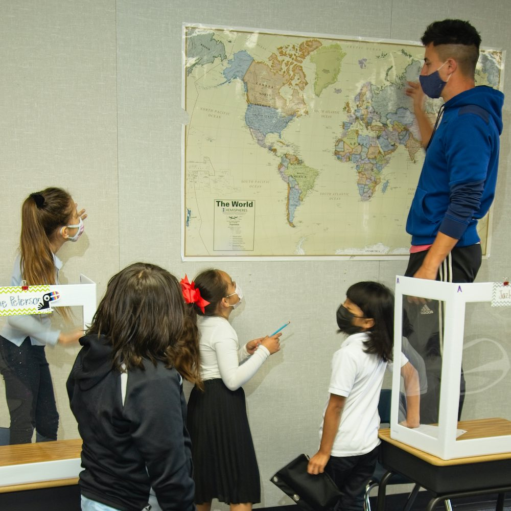 An Empower Language Academy teacher and four students look at a large map on the wall of a classroom together
