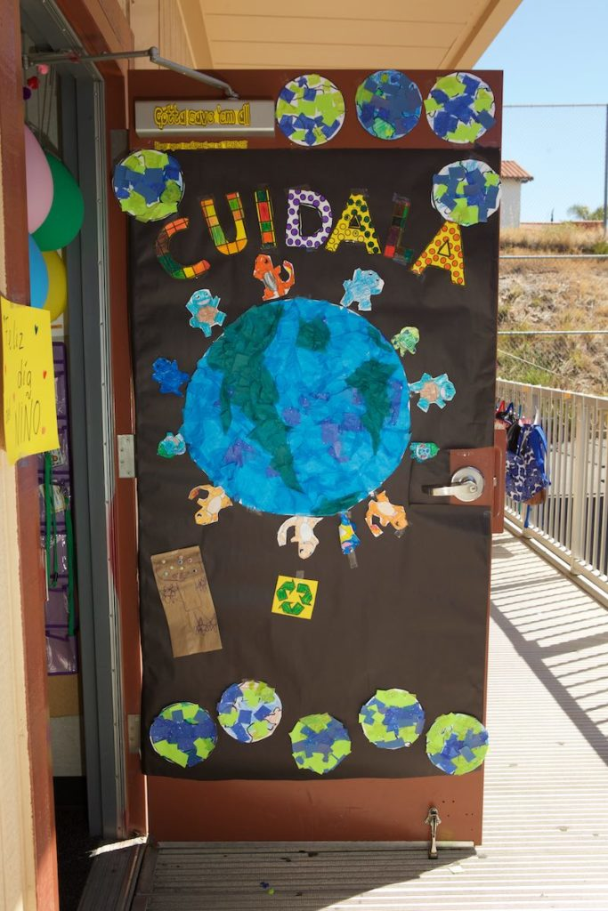 A classroom door at Empower Language Academy with child created images of the earth and animals with a sign that says CUIDALA